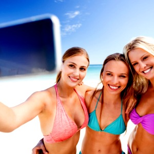 Girls taking a group selfie photo at the beach